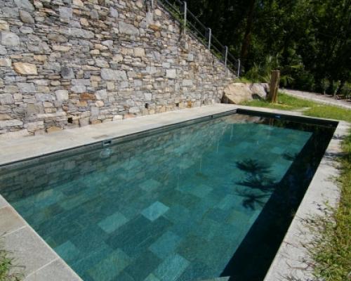 Piscina outdoor con rivestimento in pietra policroma realizzata da Piscine Verbano